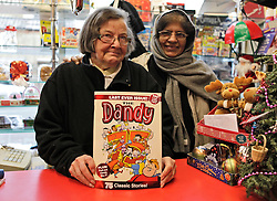 © Licensed to London News Pictures. 04/12/2012. London, U.K..Renate (left) and Farida(right) of the PAT-A-CAKE SHOP newsagents in Northwood, Harrow, show off their final Dandy comic for sale, today (04/12/12). The Dandy comic from publishing group DC Thompson, which first launched in 1937, 75 years ago today featuring characters such as Desperate Dan and Bananaman, published its final print edition after a slump in circulation. the revamped digital edition also launched today..Photo credit : Rich Bowen/LNP