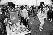 An MC dressed in a shell suit raps to the crowd in front of DJ's and other local MC's at a Hip Hop battle,Moss Side Carnival, Alexandra Park, Manchester 1989
