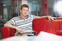 Male office worker sitting on sofa in office portrait