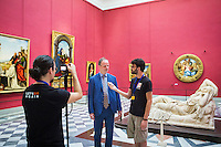 "FLORENCE, ITALY - 29 JUNE 2016: The new director of the Uffizi Gallery Eike Schmidt is interviewed by students in ""Michelangelo and the Florentines"" room at the Uffizi Gallery in Florence, Italy, on June 29th 2016.<br /> <br /> Art historian Eike Schmidt, former curator and head of the Department of Sculpture, Applied Art and Textiles at the Minneapolis Institute of Arts, became the first non-Italian director of the Uffizi in August 2015, replacing Antonio Natali who directed the gallery for 9 years. One of the main goals of the new director is to open the Vasari Corridor to the general public. Currently the corridor can only be visited with group reservations made by external tour and travel agencies throughout the year.<br /> <br /> The Vasari Corridor is is a 1-kilometer-long (more than half mile) elevated enclosed passageway which connects the Palazzo Vecchio with the Palazzo Pitti, passing through the Uffizi Gallery and crossing the Ponte Vecchio above the Arno River, in Florence. The passageway was designed and built in 1564 by Giorgio Vasari in only 6 months to allow Cosimo de' Medici and other Florentine elite to walk safely through the city, from the seat of power in Palazzo Vecchio to their private residence, Palazzo Pitti. The passageway contains over 1000 paintings, dating from the 17th and 18th centuries, including the largest and very important collection of self-portraits by some of the most famous masters of painting from the 16th to the 20th century, including Filippo Lippi, Rembrandt, Velazquez, Delacroix and Ensor."