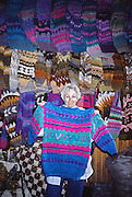 Mom shops for colorful wool sweaters on Chiloe Island, which is the largest island in Chile. Location: Isla Chiloé, Los Lagos Region, Zona Austral, Chile, South America.