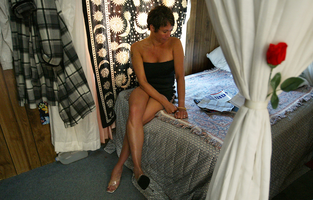 Ricki, a working girl at the Salt Wells Ranch bordello in Nevada sits in her room.