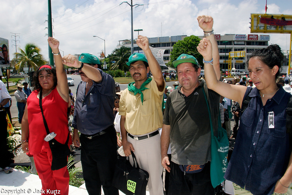 14 SEPTEMBER 2003 - CANCUN, QUINTANA ROO, MEXICO:  Farm activists from the organization Via Campesina salute, Lee Kyung-hae, at a memorial service Sunday for the Korean farm activist who publicly committed suicide Wednesday in Cancun to protest World Trade Organization agricultural policies, has been built where he died in a park in Cancun. Thousands of protestors opposed to the World Trade Organization and globalization have come to Cancun to protest the WTO meetings taking place in the hotel zone. Mexican police restricted most of the anti-globalization protestors to downtown Cancun, about five miles from the convention center.  PHOTO BY JACK KURTZ