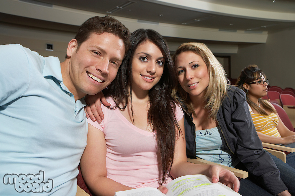 Three students smiling in class, portrait