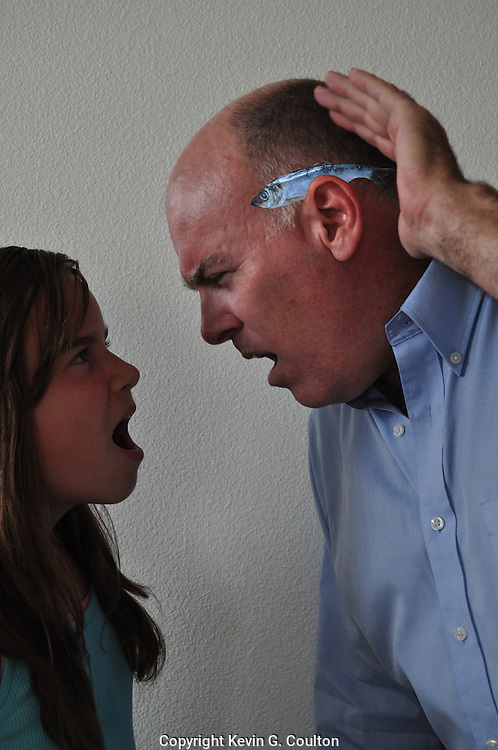 Humorous photograph of a father with a herring behind his ear and his daughter shouting at him implying that he needs a new herring (hearing) aid!