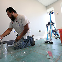 Sergio Perez puts a new coat of paint on the trim inside a newly renovated office in the BancorpSouth offices in downtown Tupelo.