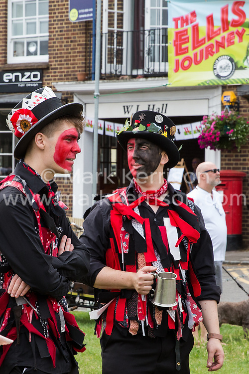 Datchet, UK. 30 June, 2019. Datchet Border Morris, an all male Border Morris side with a mixed band who perform dances in the English border Morris style, dance before the arrival of pre-1905 vehicles taking part in the 48-mile Ellis Journey from Micheldever station near Winchester to Datchet. The Ellis Journey is a reenactment of the first recorded journey by a motorised carriage in England undertaken by pioneer automobilist Hon. Evelyn Ellis in his new, custom-built Panhard-Levassor on 5th July 1895.