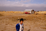 Pine Ridge Sioux Indian Reservation, South Dakota, Oglala Sioux (Lakota) young boy in front of rural home in Kyle area