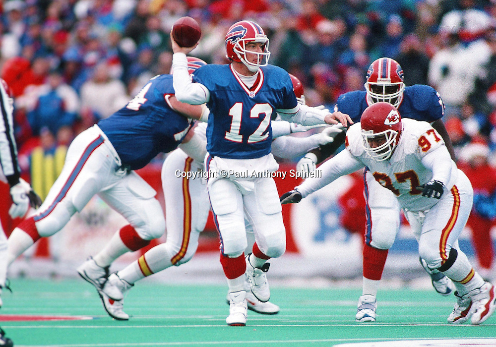 Buffalo Bills quarterback Jim Kelly (12) throws a pass while being chased by Kansas City Chiefs  defensive lineman Dan Saleaumua (97) during the NFL football game against the Kansas City Chiefs on Dec. 22, 1996 in Orchard Park, N.Y. The Bills won the game in overtime 20-9. (©Paul Anthony Spinelli)