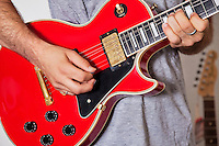 Midsection of man playing electric guitar