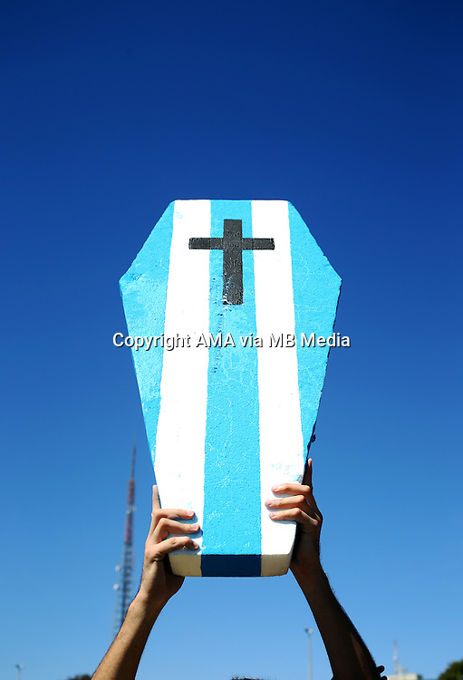 A fan of Brazil holds up a coffin painted in the colours of Argentina