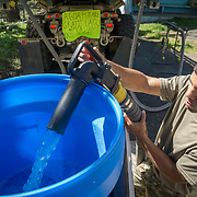OCTOBER 25 - UTUADO, PUERTO RICO - <br /> SPC Andrea Bertarello fills up a water cistern in the back of a truck from a water truck with 2,000 gallons of potable water parked near a baseball park in Utuado. Troops from Fort Bragg, NC, are using a water filtration system to purify water from the nearby Lago Dos Bocas.<br /> (Photo by Angel Valentin/Freelance)