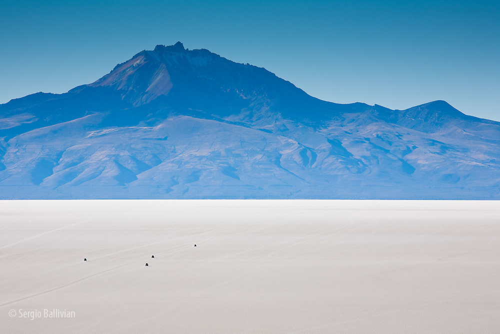Vehicles are driven towards Thunupa Volcano on seasonal informal roads that appear on the surface of the Salar de Uyuni in southwest Bolivia.