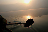 A heart shaped oar  dips in the water as  the sun rises over the horizon on Dal Lake, Kashmir.