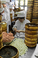 Shanghai, China - April 7, 2013: people preparing dim sum Shanghai style steamed pork dumplings at the Nanxiang Steamed bun shop in Fang Bang Zhong Lu old city at the city of Shanghai in China on april 7th, 2013