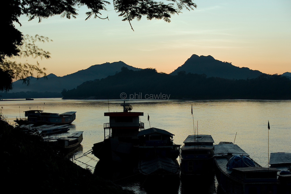 Luang Prabang, Laos - boats moored on the mekong river.
