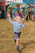 Kids enjoy the Bubble inc giant bubble makers and foam machines - The 2017 Latitude Festival, Henham Park. Suffolk 14 July 2017