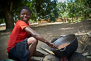 Isatu Conteh, 13 years old heats up ground peanuts over a fire in Karineh village, Magbema chiefdom, Kambia district, Sierra Leone on April 3, 2017.