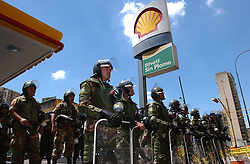 Members of the National Guard patrol outside of a shell gas station during an opposition led march.  The opposition is demanding that the National Electoral Council speed up the process leading to a presidential referendum.