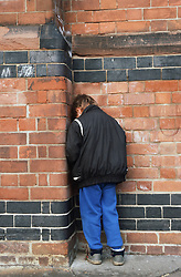 Young boy standing in corner of junior school playground facing brick wall,