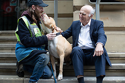 "© Licensed to London News Pictures. 20/06/2019. Manchester, UK. In one of his last actions as Liberal Democrat Party leader , SIR VINCE CABLE meets Big Issue seller JUSTIN GREEN (49) and his dog BUMPER (ten) in Manchester City Centre . The party say they are highlighting what they call a "" Homeless Tax "" , which they oppose , and which could see fines of up to £1,000 imposed upon the homeless by Manchester City Council . The final Local Government Information Unit (LGiU) report from the Local Government Homelessness Commission (LGHC) – a year-long initiative set up to investigate how councils can fulfil their obligation to prevent homelessness - is due to be published . The Liberal Democrats will appoint a new leader in July . Photo credit: Joel Goodman/LNP"