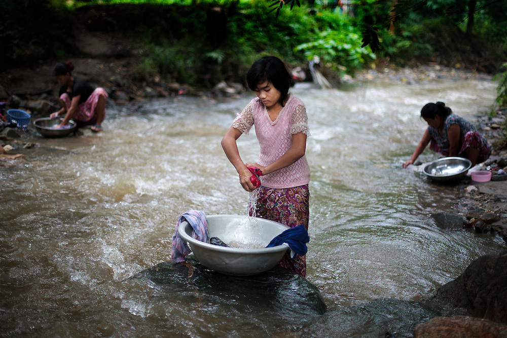 Nmau Hkawn Htoija, 14, from Shadanpa village, wash the clothes in a river near to Woi Chyai Internal Displacement People refugee camp where she live in Laiza village close to the China border, Myanmar on July 31, 2012. According to KIO (Kachin Independence Organization) sources around 50000 Kachin people live as refugees in those camps.