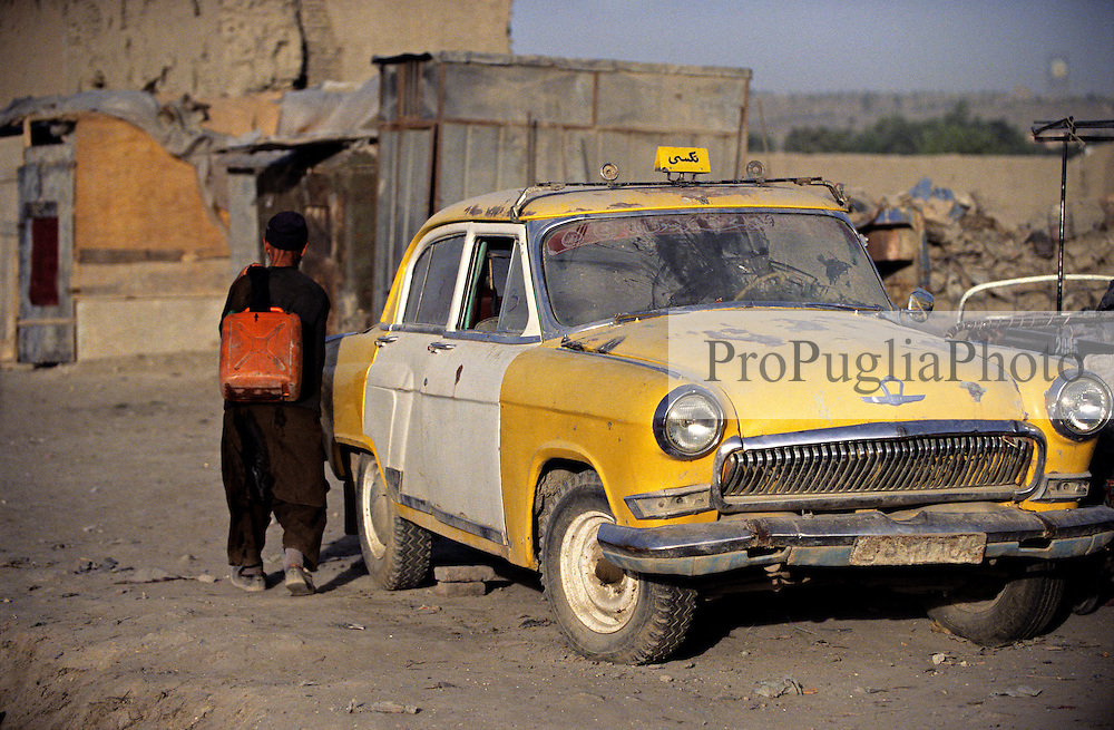 A yellow taxi is parked off road,  an elderly man carries a tank of water on his back.