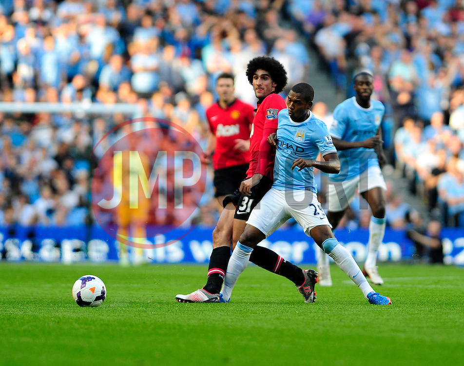 Manchester United's Marouane Fellaini is challenged by Manchester City's Fernandinho - Photo mandatory by-line: Dougie Allward/JMP - Tel: Mobile: 07966 386802 22/09/2013 - SPORT - FOOTBALL - City of Manchester Stadium - Manchester - Manchester City V Manchester United - Barclays Premier League