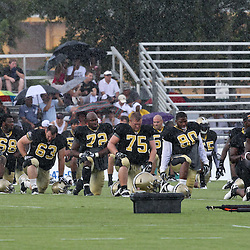 August 9, 2011; Metairie, LA, USA; New Orleans Saints players stretch  in a rain storm during training camp practice at the New Orleans Saints practice facility. Mandatory Credit: Derick E. Hingle