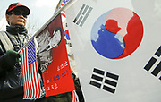 True believers in late President Park Chung-Hee and his daughter and current President Park Geun-Hye hold the Stars and Stripes and South Korean flags during a rally staged to support the president near the Constitutional Court in Seoul, South Korea, Mar 9, 2017, a day before the Constitutional Court's ruling on President Park Geun-Hye's impeachment. Park was impeached by the national assembly last December for allegedly letting her long time friend Choi Soon-sil meddle in state affairs and colluding with her to extort millions of dollars from chaebols, including Samsung. The ruling on her impeachment will be delivered by the court at A.M. 11:00 local time (02:00 GMT) on Friday, March 10, 2017. If the Constitutional Court upholds the impeachment, President Park should leave office permanently and presidential election is expected to he held on May 9, 2017. Photo by Lee Jae-Won (SOUTH KOREA) www.leejaewonpix.com