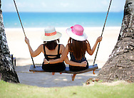 Two young women hugging on swing. Palawan