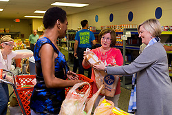 Keeneland employee Amy Petit, center and Amy Gregory, right, guide Barbara Turley of Lexington through her food distribution day at a God's Pantry Distribution site, Tuesday, April 18, 2017 at Broadway Christian Church in Lexington.