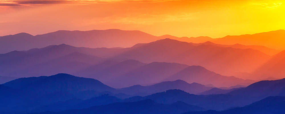 A panoramic view of a sunset over the Blue Ridge Mountains from an overlook  on the Blue Ridge Parkway in North Carolina.  The setting sun turned the sky orange as it illuminated the tops of the various mountains.