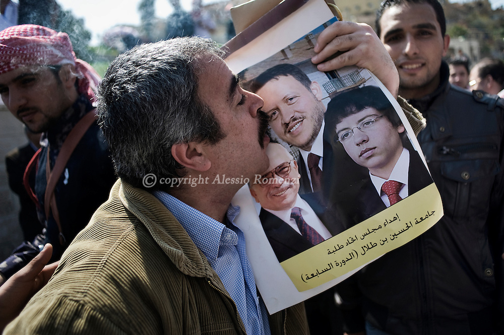 ORDAN, Amman : Jordanian government supporters kissing a portrait of Abd Allah ll, his father King Husain and his son prince Hussein in front of the old palace during a gathering in support of King Abdullah II in the capital Amman March 26, 2011 as Jordan's Islamist opposition, leftists and trade unions demanded the ouster of Prime Minister Maaruf Bakhit, blaming him for violence that has killed one person and injured 130.ALESSIO ROMENZI