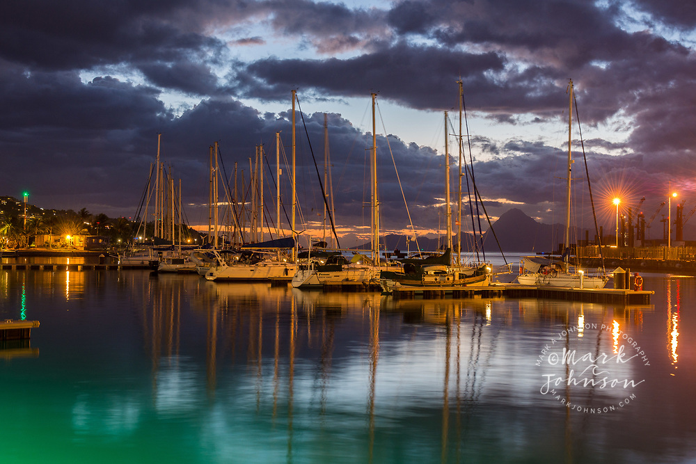 Boats moored in Papeete Harbor, Tahiti, French Polynesia. Moorea island in the background