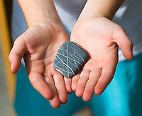 A childs hands holding a striped rock