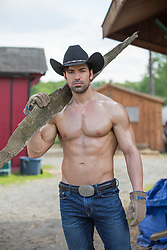 shirtless muscular cowboy carrying wood on a ranch