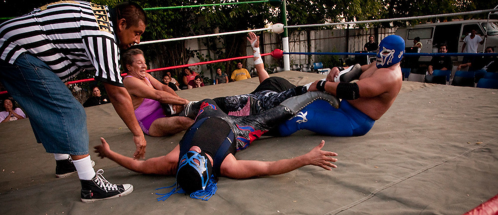 """Lucha Libre, where the air is hot, 100+ degrees in the shade in the shade, and so is the wrestling in San Antonio's Southside. With a community that is nearly 100% Hispanic the crowds here are not at all frightened by these masked men with bad attitudes and flare foe color. From all walks of life,  Luchadores don costumes and fly at eachother for the entertainment of boisterous crowds that are encouraged to root for, taunt and shoot """"silly string"""" at the wrestlers.  Referees seem to miss wrestling rule infractions and very bad sportsmanship.  (From Wikipedia) Lucha libre (Spanish for """"free wrestling"""" or free fighting) is a term used in Mexico, and other Spanish-speaking countries referring to a form of professional wrestling involving varied techniques and moves.  Mexican wrestling is characterized by rapid sequences of holds and moves, as well as 'high-flying moves', some of which have been adopted in the United States, and colorful masks. Photo by and copyright 2009, Lance Cheung"""
