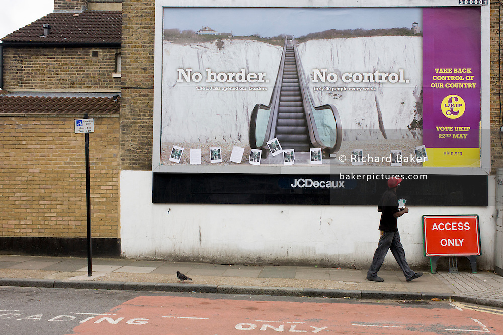 Passing voter and the anti-EU 'UK Independence Party's (UKIP) political billboard shows an escalator leading up the white cliffs of Dover (a metaphor for unrestricted immigration access to Britain) in East Dulwich - a relatively affluent district of south London. The ad is displayed before European elections on 22nd May and UKIP's controversial right-wing policy of no foreigners into the UK to take British jobs, is promising to do well in the forthcoming election.