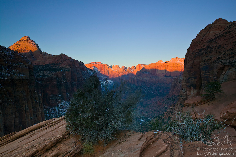 The rising sun lights up several prominent peaks in Zion National Park, Utah, including the Towers of the Virgin. The peaks, from left-to-right: The Watchman, The West Temple, The Sundial, The Altar of Sacrifice, The Sentinel, The Streaked Wall, and the East Temple. The Zion Canyon overlook overlooks both the Zion Canyon at the back of the frame and the Pine Creek Canyon near the foreground.