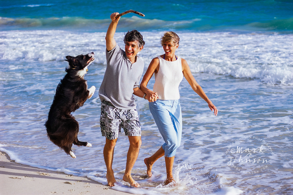 Hawaii, USA --- Couple playing with Dog