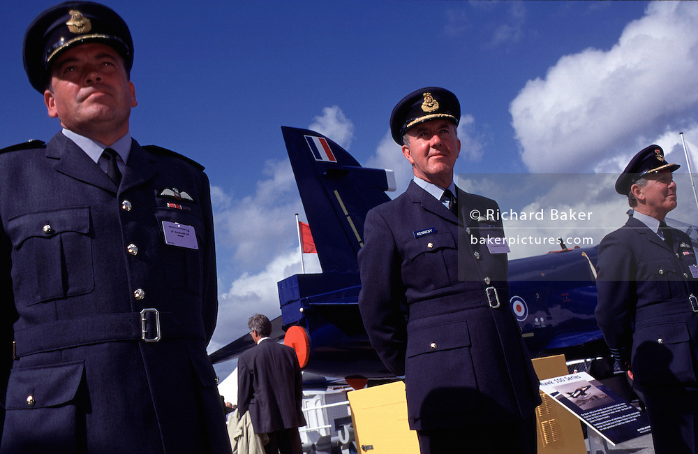 Royal Air Force officers formally await visiting foreign dignitaries at the BAE Systems stand during the bi-annual aerospace industry expo at the Farnborough airshow in southern England. As an important trading partner, both the RAF and BAE Systems present a united front in the marketplace, each helping the other to promote the UK-PLC  brand and urging foreign governments to buy British. In the background is a BAE Systems Hawk attack and trainer jet aircraft used by the RAF and airforces in gthe middle-east. Operators of the Hawk include the Royal Air Force (notably the Red Arrows display team) as well a considerable number of foreign military operators. The Hawk is still in production in the UK and under licence in India by Hindustan Aeronautics Limited (HAL) with over 900 Hawks sold to 18 operators around the world.