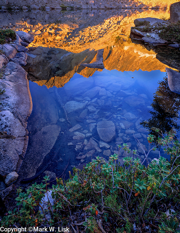 Granite Peaks reflect into the rocky shore of  lower Profile Lake in the Sawtooth Wilderness.