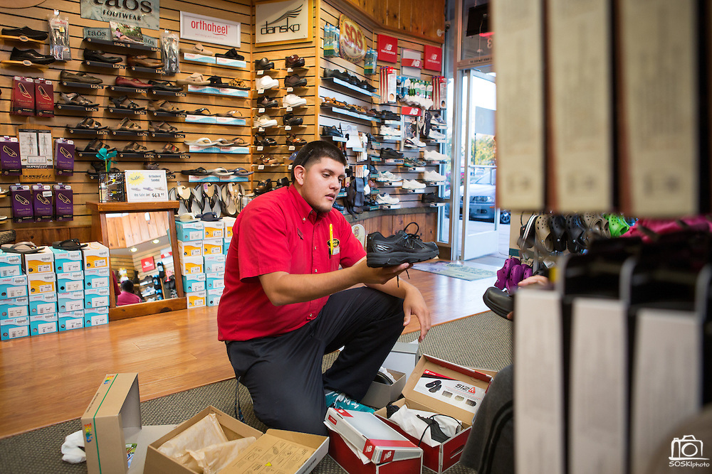 Store manager Mark Coutreras explains the difference between the soles of two pairs of shoes, which can lead to a safer workday, to customer Yany Orona at Beck's Shoes in Milpitas, Calif., on Sept. 18, 2012.  Photo by Stan Olszewski/SOSKIphoto.