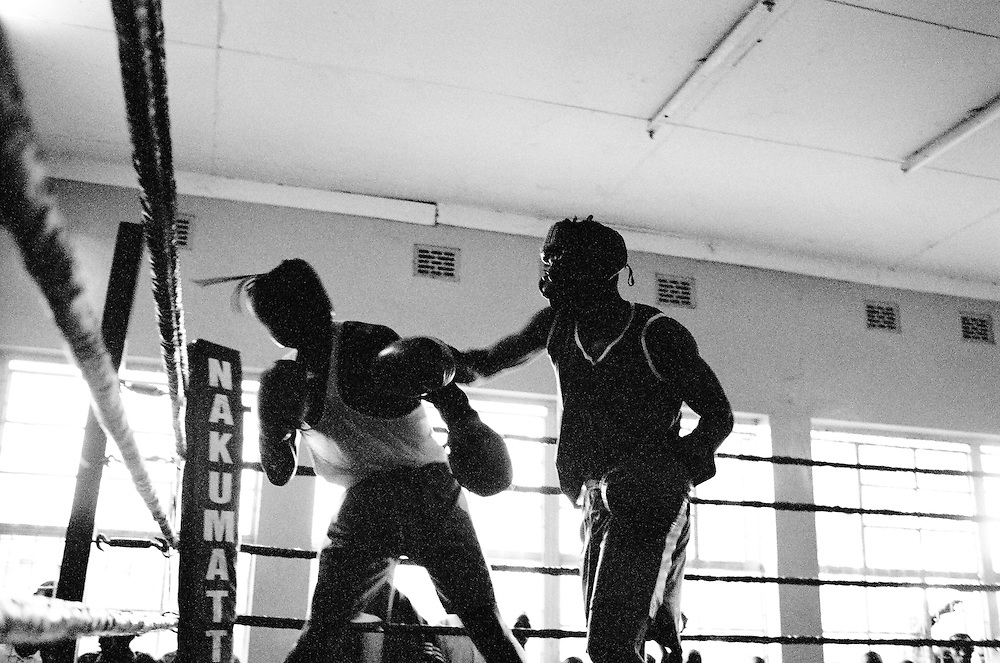 NAIROBI, KENYA - MARCH 18, 2010: Athletes spar during a boxing tournament featuring the Kibera Olympic Boxing Club, Kenya Prisons and the Kenya Police and Armed Forces (AFABA). Each year, Kibera Olympic boxers aspire individually to make the national team, and the opportunity to compete in the annual Kenya Open boxing tournament. In previous years, boxers from Kibera slum have gone on to win tournaments on both the national and international stage.<br /> <br /> Within Kenya's progressive youth culture is the Kibera Olympic Boxing Club, a group of low-income adolescents from the slum whose leader uses boxing as a way to engage with idle youth. The group's ethnic diversity is remarkable given Kenya's 2008 post-election violence in which people from several tribes were forced violently out of slums. Together, these boxers represent a nascent trend of cross-tribe brotherhood in a healing nation.