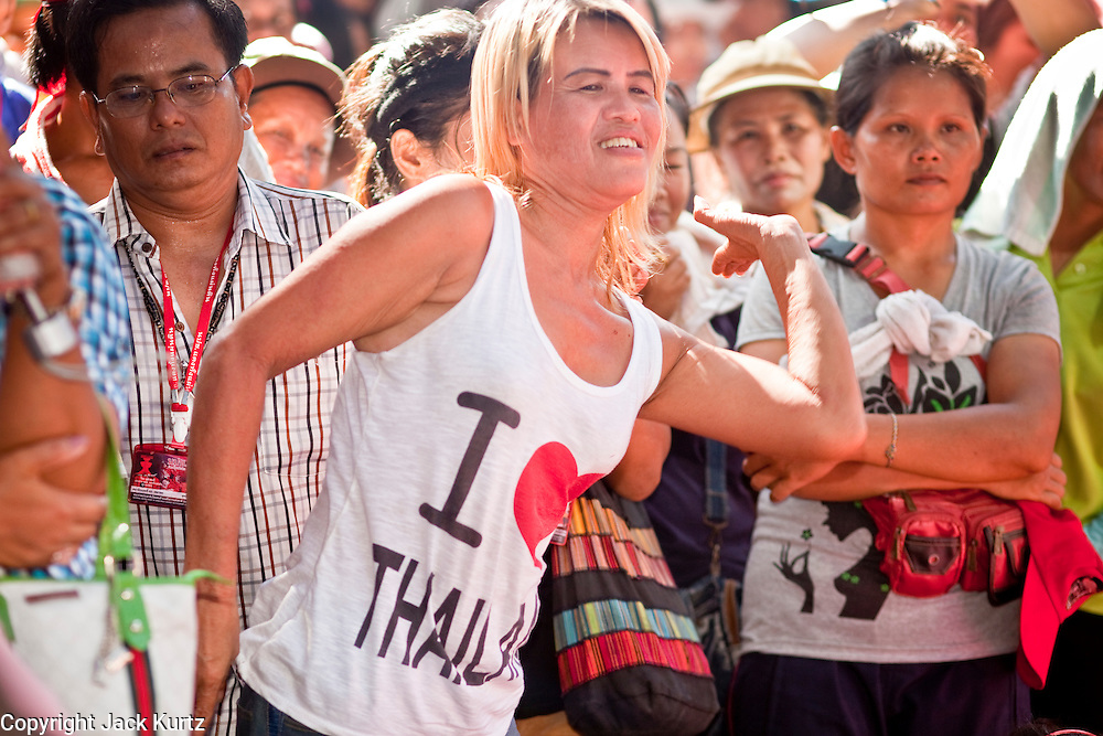 "09 MAY 2010 - BANGKOK, THAILAND: A Red Shirt dances during the Red Shirt rally in Bangkok Sunday. The Red Shirt leaders said Sunday they still conditionally supported the Prime Minister's ""Road Map to Reconciliation"" but that their opponents the Yellow Shirts needed to sign on to make the five point ""Road Map"" viable. About 5,000 people mostly from northeast Thailand, joined the Red Shirts in Ratchaprasong over the weekend. Members of the United Front of Democracy Against Dictatorship (UDD), also known as the ""Red Shirts"" and their supporters have occupied Ratchaprasong intersection, the site of Bangkok's fanciest shopping malls and several 5 star hotels, since April 4. The Red Shirts are demanding the resignation of current Thai Prime Minister Abhisit Vejjajiva and his government. The protest is a continuation of protests the Red Shirts have been holding across Thailand. They support former Prime Minister Thaksin Shinawatra, who was deposed in a coup in 2006 and went into exile rather than go to prison after being convicted on corruption charges. Thaksin is still enormously popular in rural Thailand.   PHOTO BY JACK KURTZ"