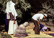 Three women behind two men perform noon prayers on a straw mat in a private garden.
