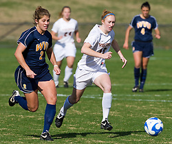 Virginia Cavaliers forward Maggie Kistner (16) dribbles up field past West Virginia Mountaineers defender Kelsey Fowler (2).  The #16 ranked Virginia Cavaliers defeated the #12 ranked West Virginia Mountaineers 3-2 in the second round of NCAA Division 1 Women's Soccer Tournament at Klockner Stadium on the Grounds of the University of Virginia in Charlottesville, VA on November 16, 2008.