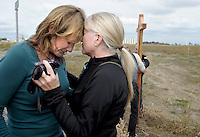 Debbie Campbell,left, is comforted by Kelly Schumacher  while friends erect a 9-foot cross at the intersection of Highway 20 and Acacia Avenue in memory of her boyfriend Paul John Hendrickson on Friday, Oct. 22, 2010. Debbie Campbell was injured in the fatal accident that took the life of her boyfriend in May.