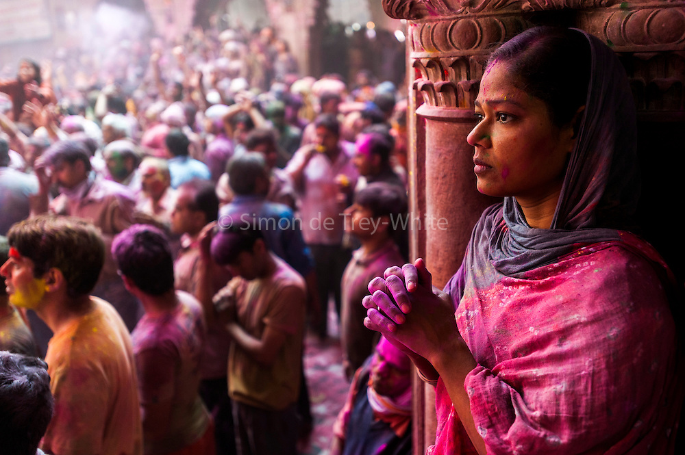 A woman prays quietly as Hindu's celebrate Holi in the Banke Bihari Temple in Vrindavan, in the Mathura district of Uttar Pradesh, India ,1st March 2010. <br /> <br /> Holi, also called the Festival of Colours, is a spring festival celebrated by Hindus, Buddhists, Sikhs, Jains and others. It is primarily observed in India, Nepal, Srilanka, Pakistan, Bangladesh, and countries with a large Indian diaspora populations, such as Suriname, Guyana, South Africa, Trinidad, UK, USA, Mauritius, and Fiji. In West Bengal of India and Bangladesh it is known as Dolyatra (Doul Jatra) or Basanta-Utsav (&quot;spring festival&quot;). The most celebrated Holi is that of the Braj region, in locations connected to the god Krishna: Mathura, Vrindavan, Nandagaon, and Barsana. These places have become tourist destinations during the festive season of Holi, which lasts here to up to sixteen days.<br /> The main day, Holi, also known as Dhulheti, Dhulandi or Dhulendi, is celebrated by people throwing coloored powder and colored water at each other. Bonfires are lit the day before, also known as Holika Dahan (burning of Holika) or Chhoti Holi (little Holi). The bonfires are lit in memory of the miraculous escape that young Prahlad accomplished when Demoness Holika, sister of Hiranyakashipu, carried him into the fire. Holika was burnt but Prahlad, a staunch devotee of god Vishnu, escaped without any injuries due to his unshakable devotion. Holika Dahan is referred to as Kama Dahanam in Andhra Pradesh.<br /> <br /> PHOTOGRAPH BY AND COPYRIGHT OF SIMON DE TREY-WHITE<br /> <br /> + 91 98103 99809<br /> email: simon@simondetreywhite.com<br /> photographer in delhi